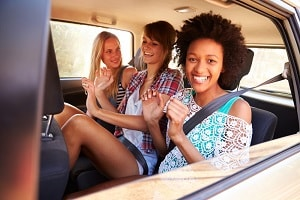 Three women passengers in the back seat of a car
