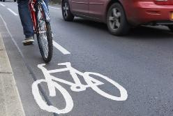 A Bicyclist Riding Alongside a Red Car