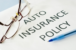 Auto Insurance Policy Paperwork With a Pen and Glasses