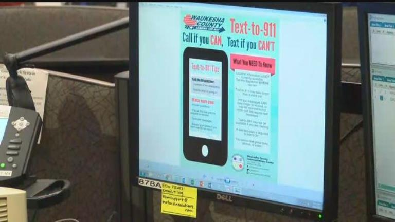 Computer monitor with flyer saying you can text 911