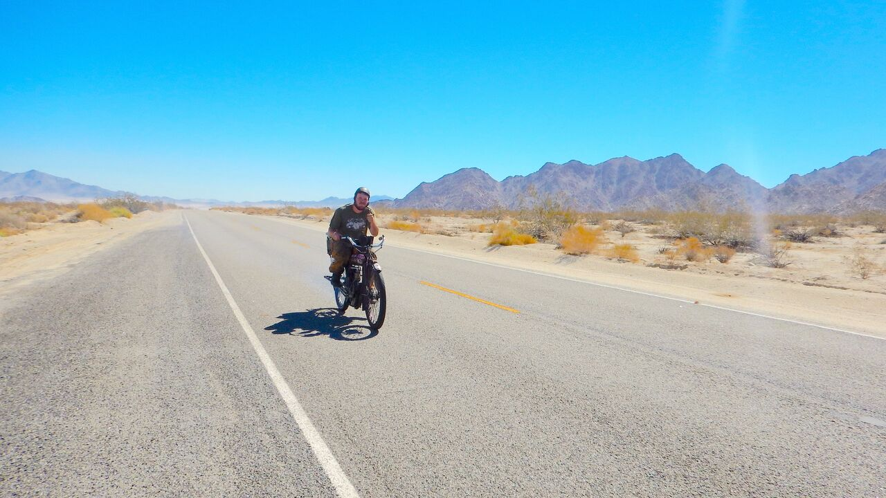 Man riding a bike on an empty road