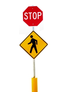 a stop sign with a yellow pedestarian sign