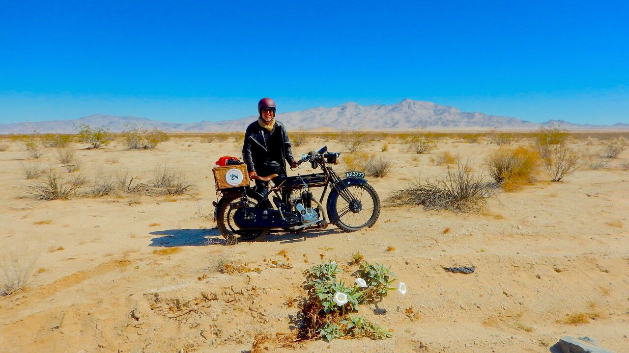 women with her bike surrounded by sand and mountains