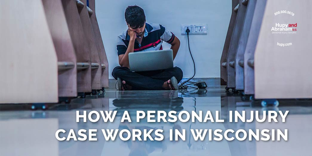 boy sitting on the floor with laptop and chargers with text How a personal injury case works in Wisconsin