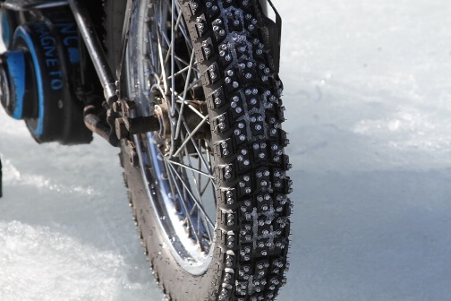 Motorcycle tire with studs for traction on ice