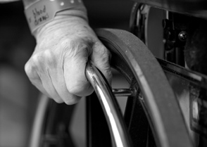 Someone in a wheelchair with focus on their hand and the wheel