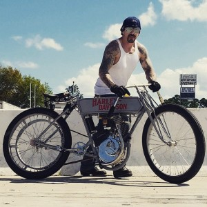 Bike builder Billy Lane standing behind a vintage Harley Davidson