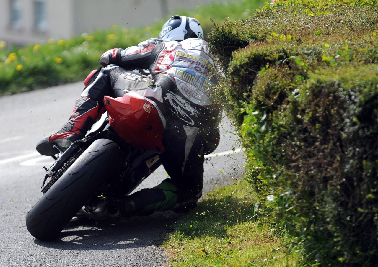 Rear view of motorcycle racer leaning into corner inches from schrubs