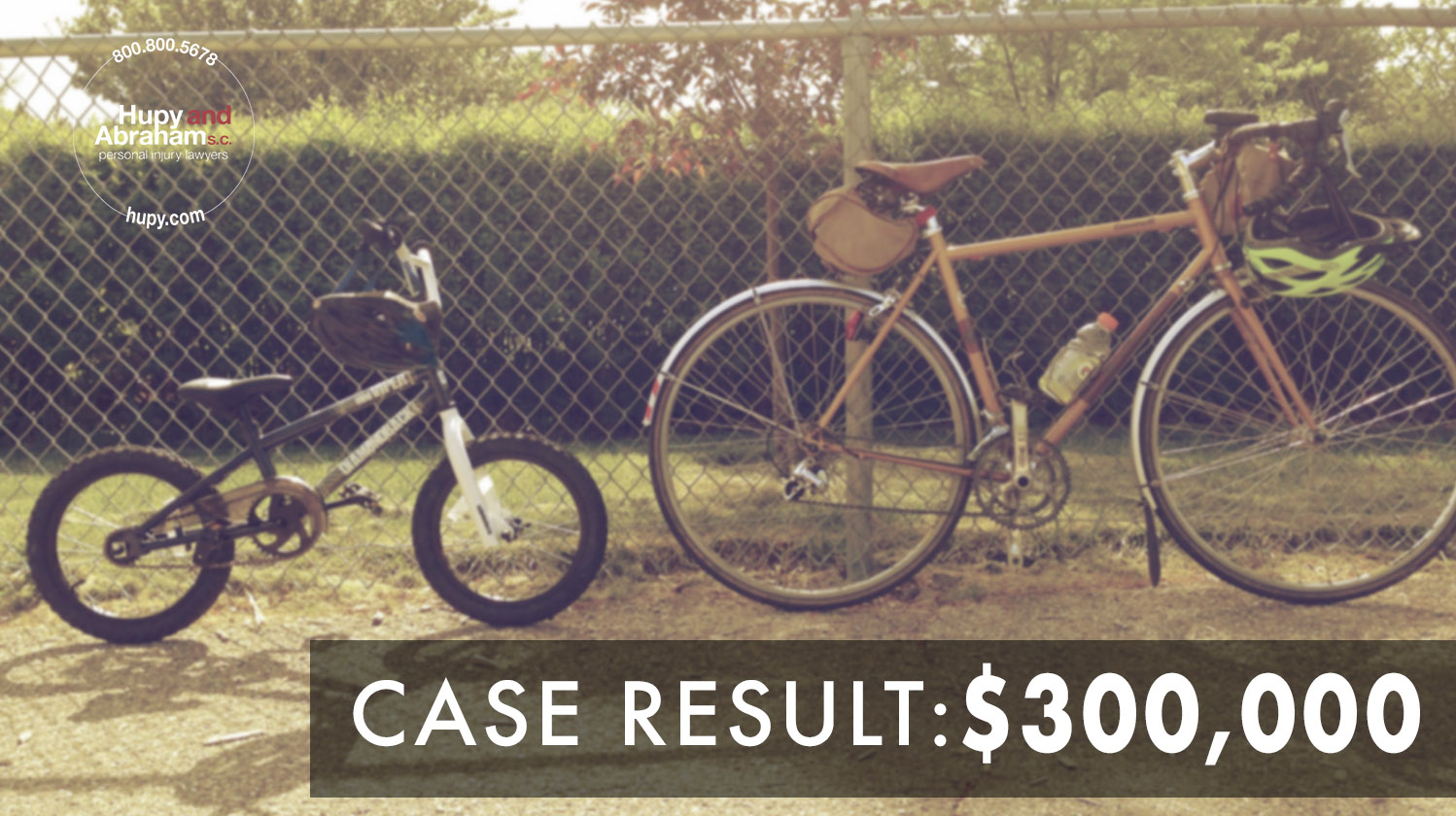 Two bicycles leaned up against a chain link fence