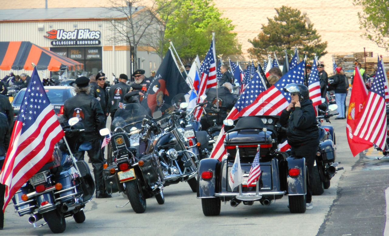 Many motorcycles with American Flags at 11th Annual Support the Troops Ride