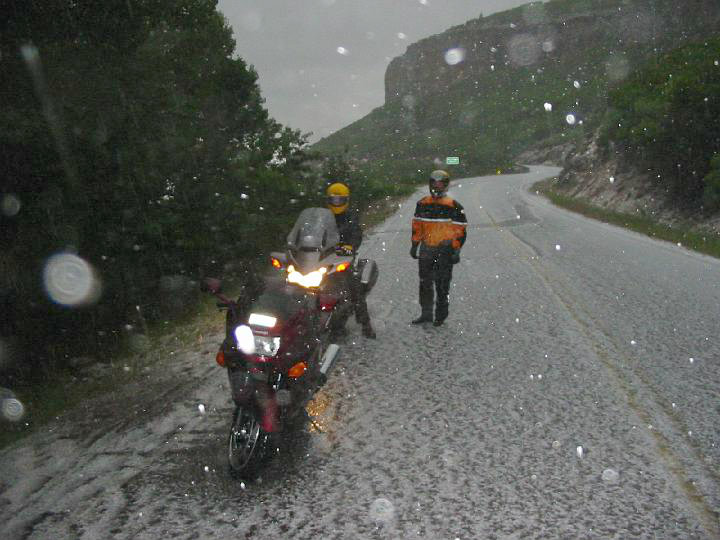 Two motorcycles and riders parked along road during heavy hail storm