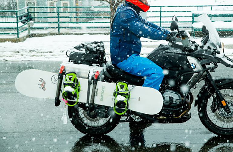Motorcycle rider in Colorado with snowboard strapped to his bike