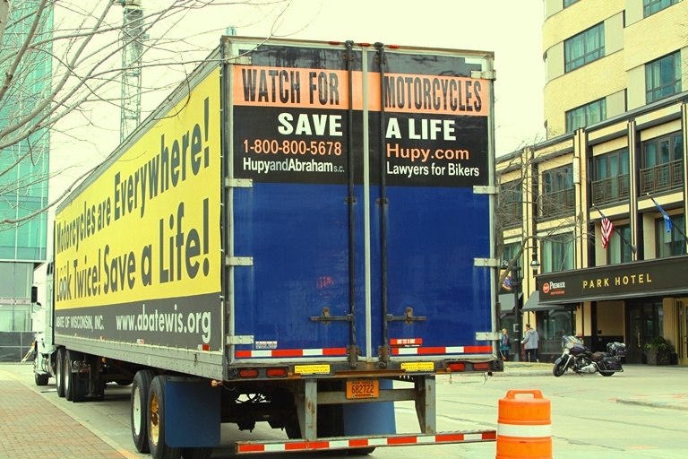 back of semi truck with text saying Watch for motorcycles, Save a  life with number and website of Hupy and Abraham