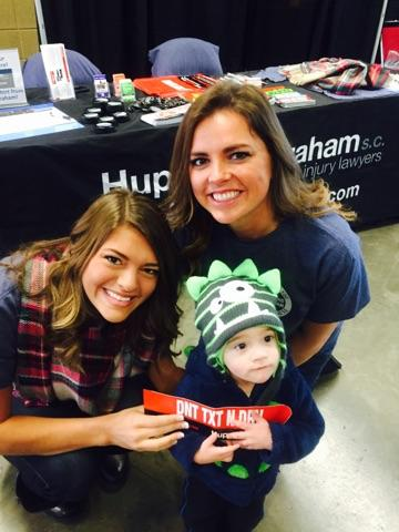 Hupy and Abraham employees and a toddler supporting the Iowa Wild