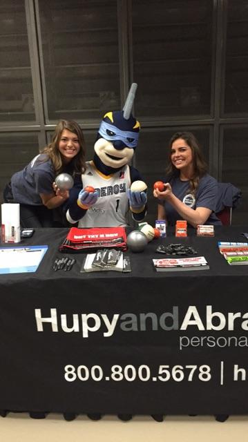 Two volunteers workingg a booth at an Iowa Energy game