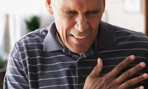 Man holding on to his heart wincing in pain