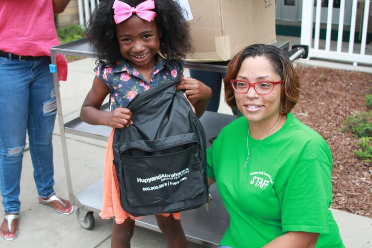 Student receiving a Hupy and Abraham backpack at last year's Open House!