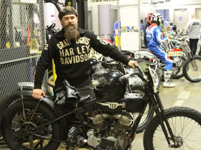 Man standing by vintage motorcycle at Flat Out Friday