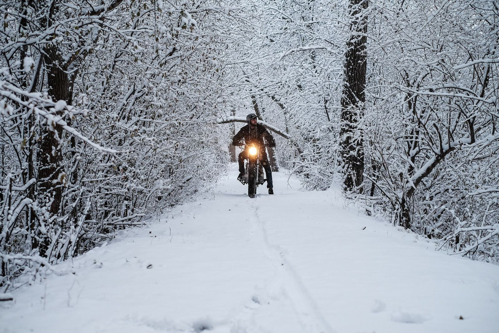 Motorcyclist riding bike on snowy road in the distance