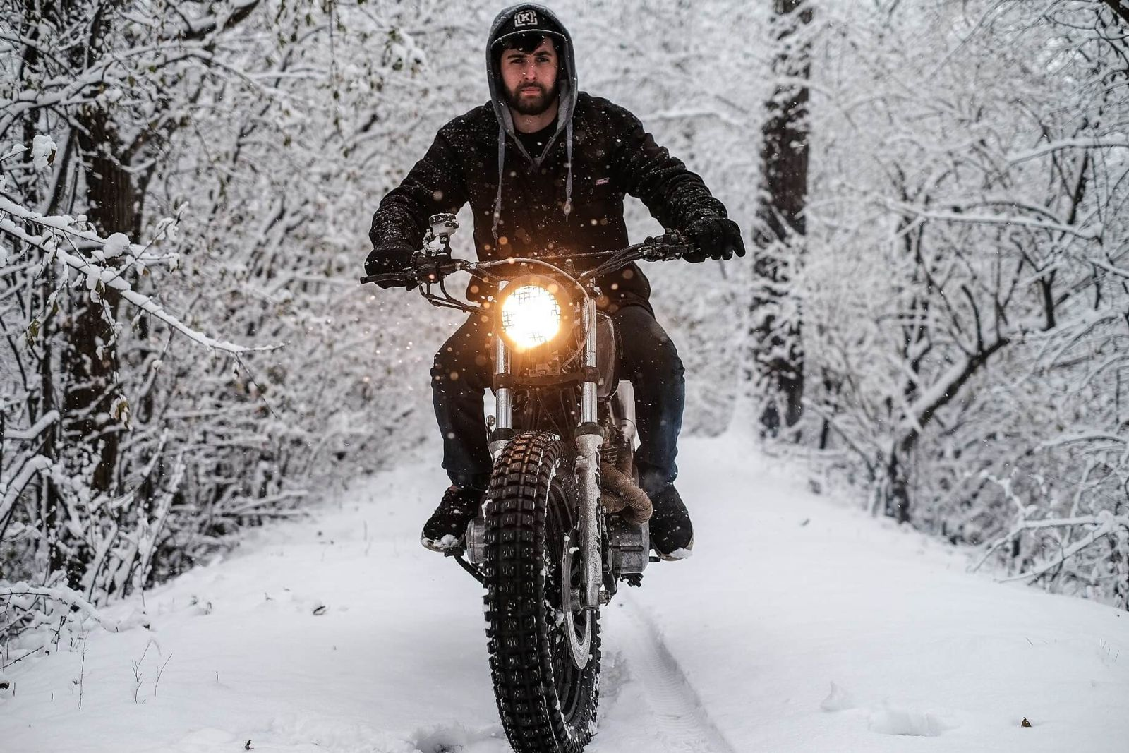 Motorcyclist riding bike on snowy country road