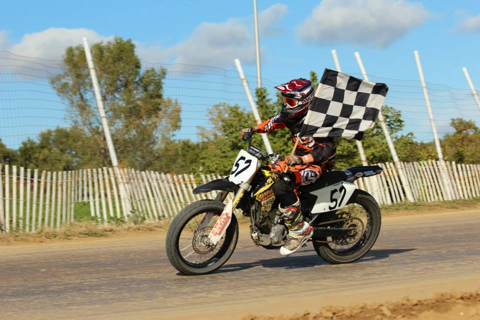 Motorcycle racer holding checkered flag after race