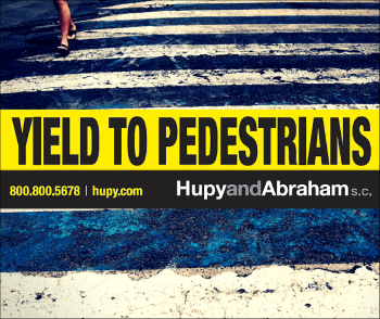 Yellow yeild to pedestrians sticker with crosswalk in background