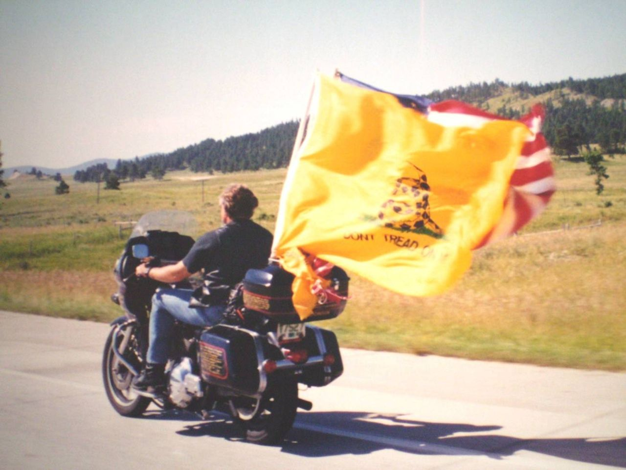 Man riding motorcycle out in the country with yellow Don't Tread on Me flag