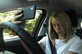 Woman taking selfie while driving