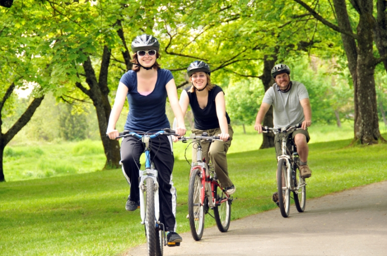 Three people on a bicycle ride through park area