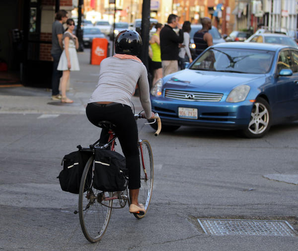 Woman on bicycle crossing the street
