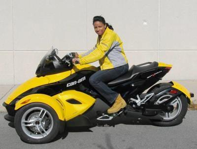 Woman sitting on three wheeled motorcycle