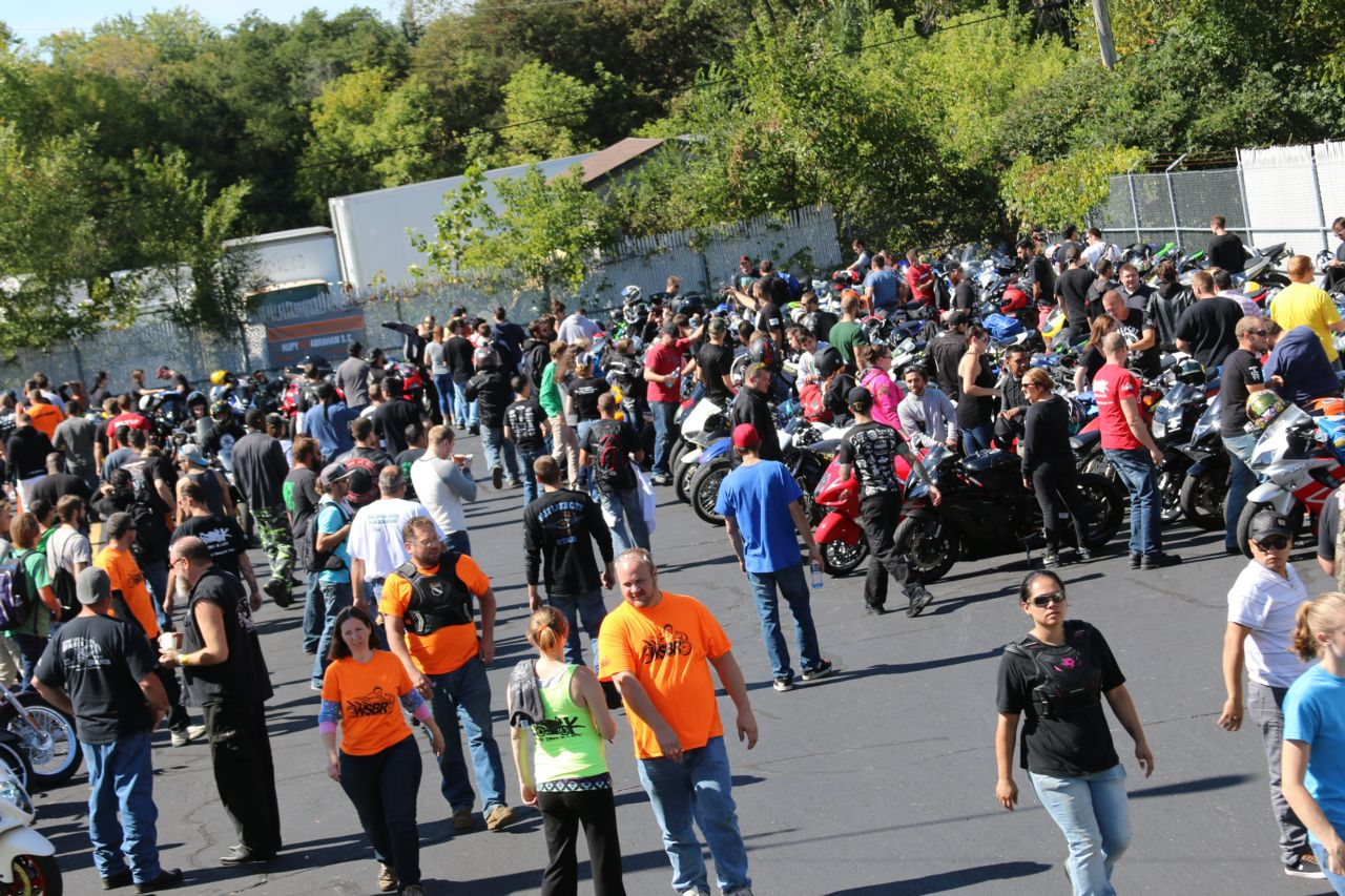 Large crowd of people in parking lot looking at motorcycles