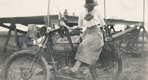 Woman wearing dress on vintage motorcycle