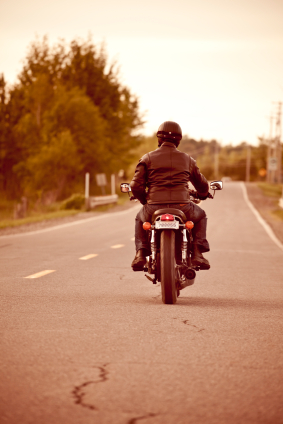 A motorcyclist driving down a road. He is wearing protective outerwear and a helmet.