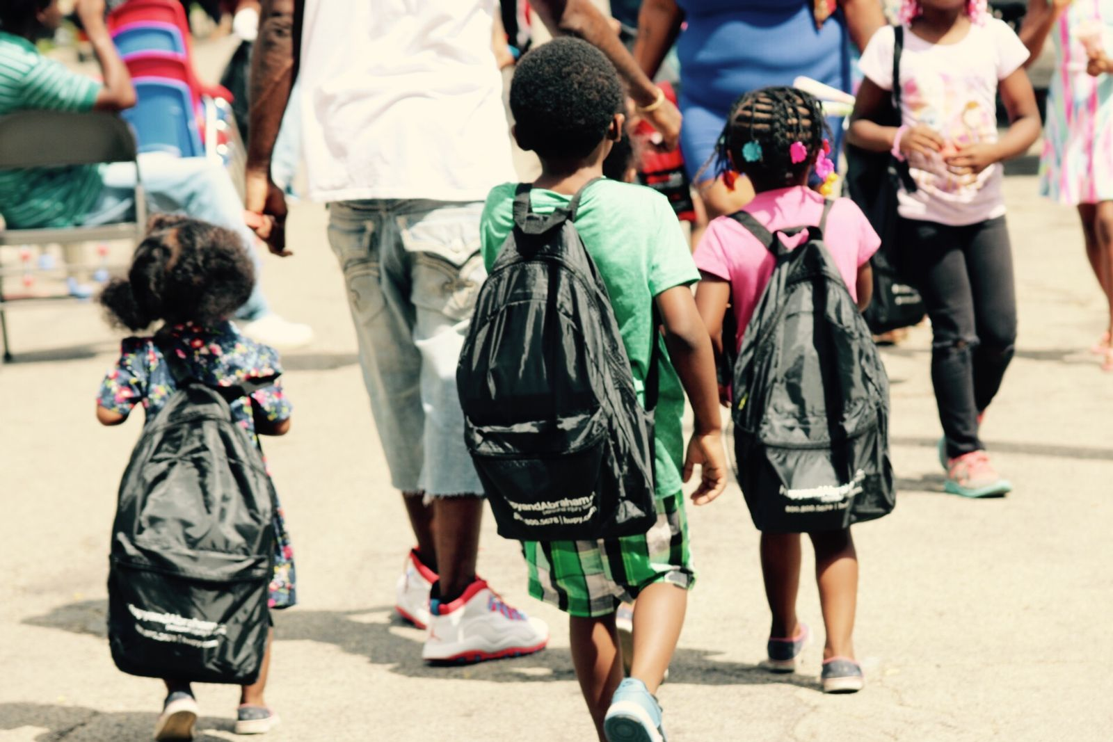 Kids with new backpacks walking to school