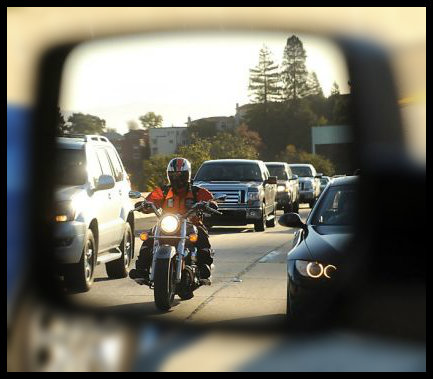 side mirror of car with motorcycle in view