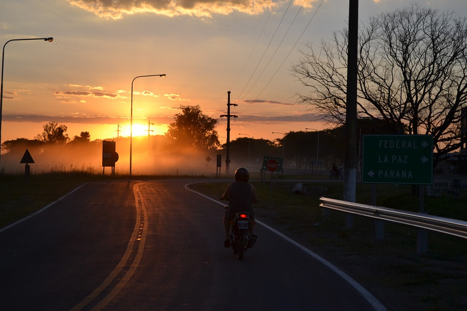 Motrocyclist driving on open road during evening