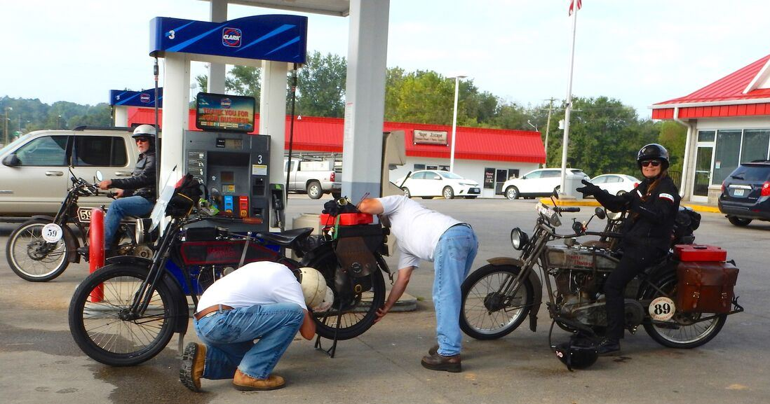 Bikers helping each other by pushing the cycle to the gas station