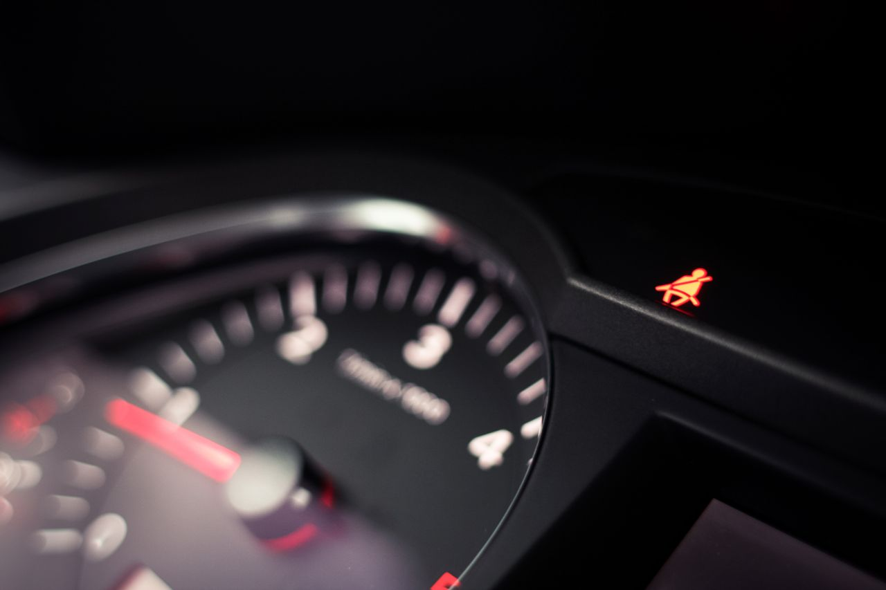 Dashboard of a car with seatbelt warning sign on