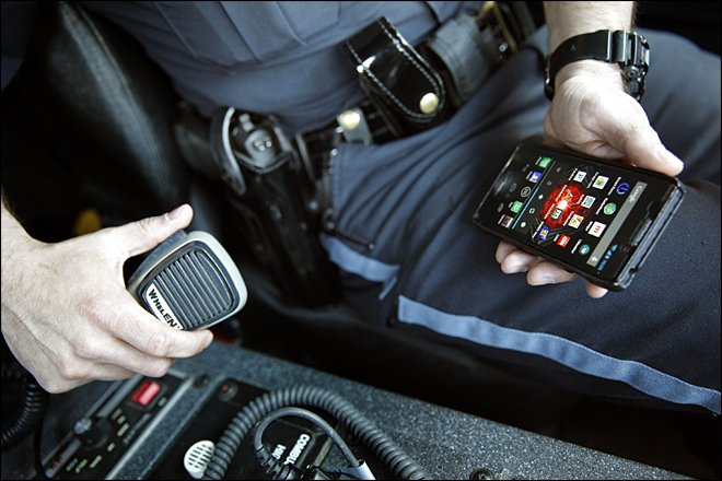 police officer holding cell phone while driving