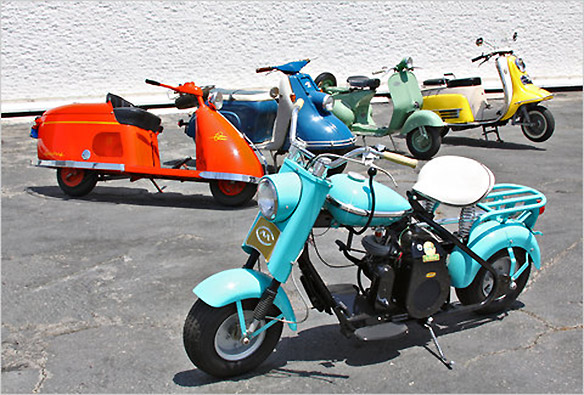 Five scooters parked in a lot