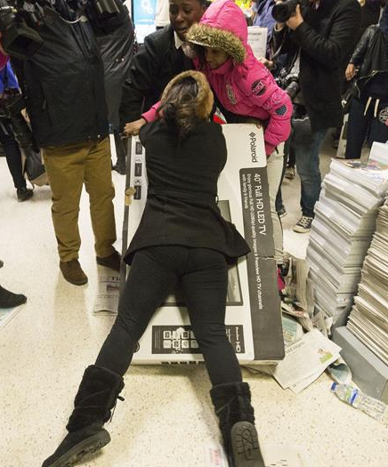 Women fighting over large TV while shopping