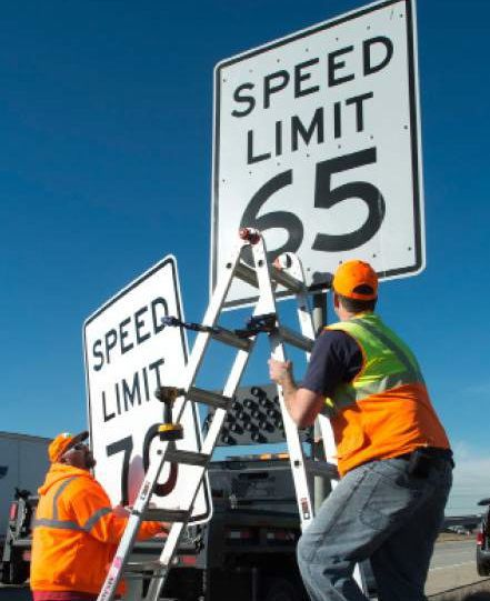 road crew changing speed limit signs