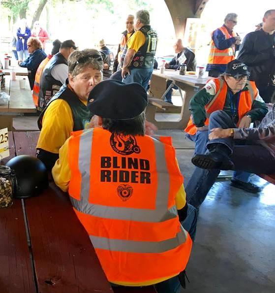 Blind motorcycle rider wearing orange blind rider vest