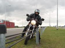 Man on motorcycle hitting wire barrier