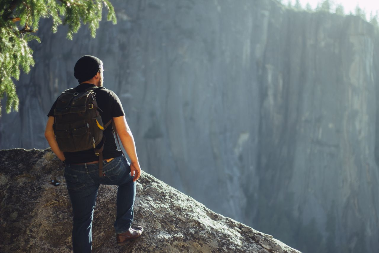 man looking out from mountain peak