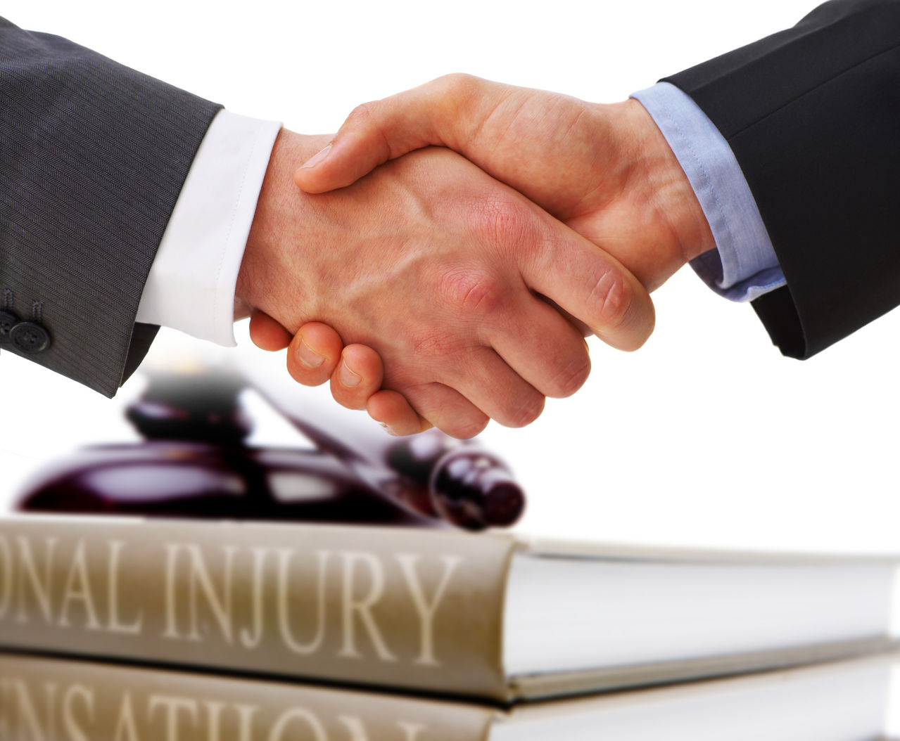 two white men in suits shaking right hands in front of a personal injury book and gavel