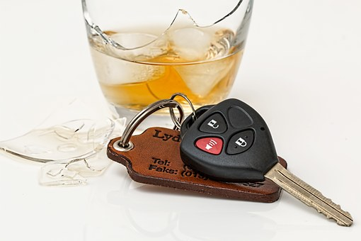 Car keys laying down by alcoholic drink