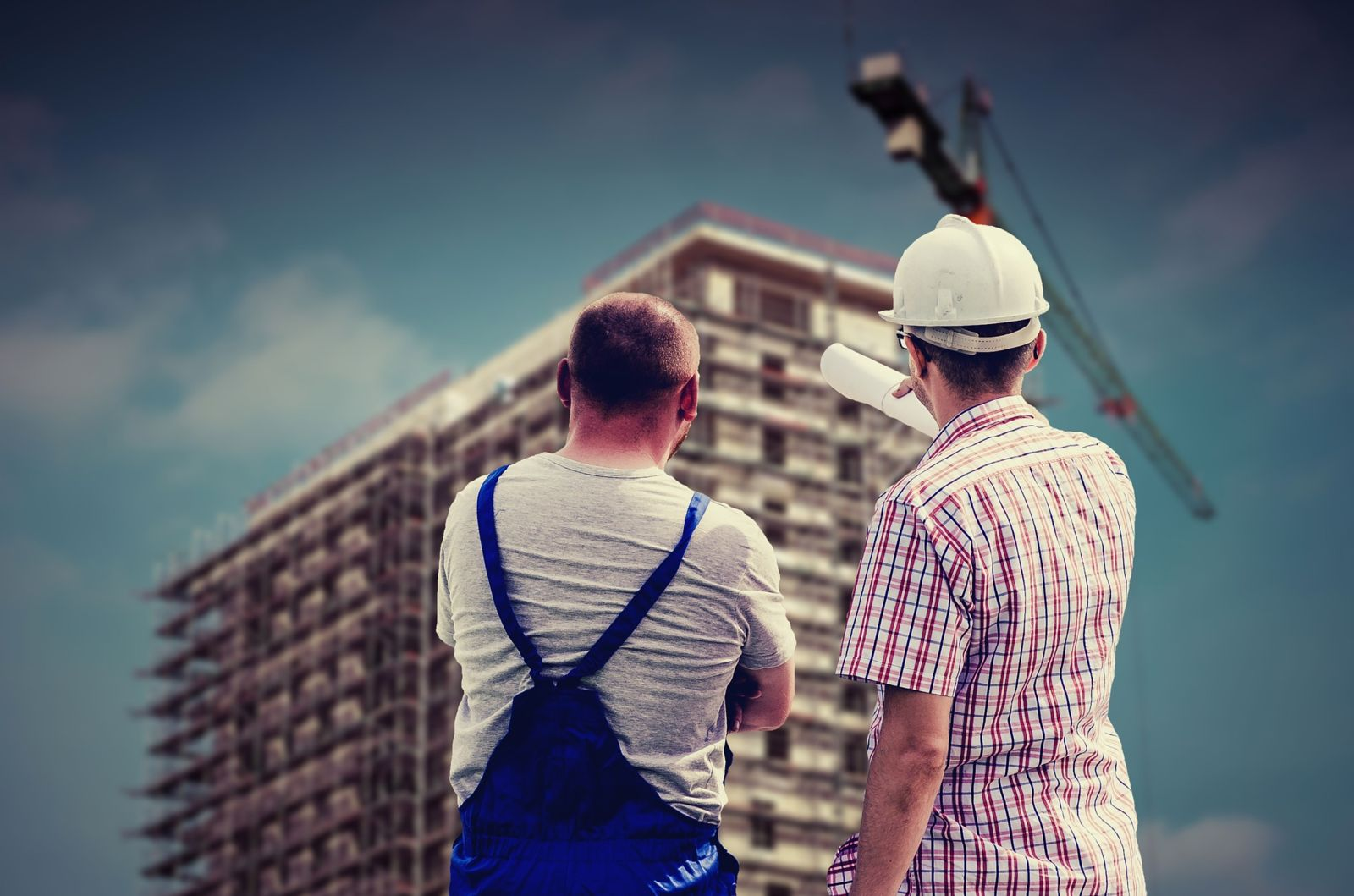 Construction workers overseeing building being built by crane in background