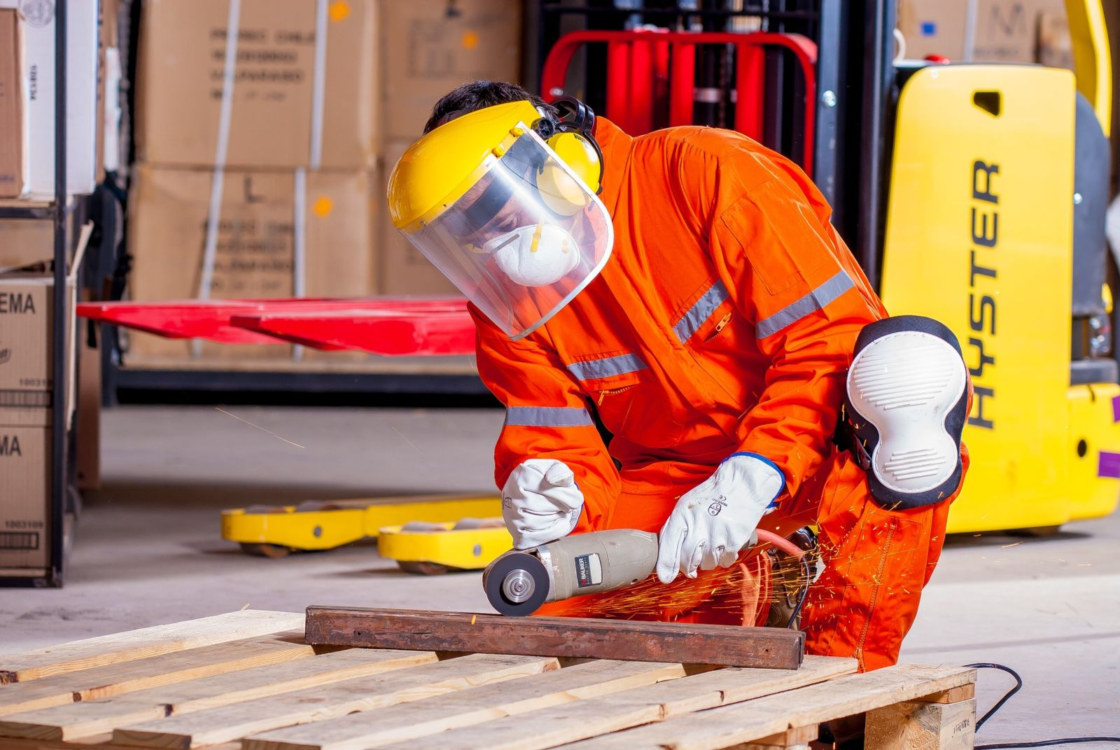 Worker in orange jump suit and has a face shielding using saw on a block of metal